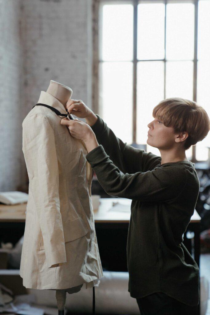 Eine Schneiderin arbeitet an einem Kleid auf einer Schaufensterpuppe